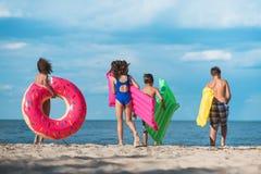 задний взгляд группы в составе дети с раздувными тюфяками идя на пляж Стоковая Фотография