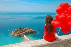 Задний взгляд девушки в красном платье над островом Sveti Stefan в Budva Стоковая Фотография RF