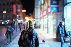 Задний взгляд девушки идя на улицу города на ноче Стоковое Изображение RF
