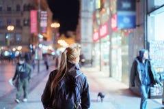 Задний взгляд девушки идя на улицу города на ноче Стоковая Фотография
