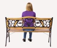 Задний взгляд женщины сидя на стенде Стоковое фото RF