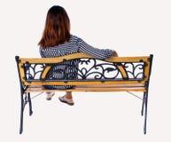 Задний взгляд женщины сидя на стенде Стоковое Фото