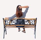 Задний взгляд женщины сидя на стенде Стоковая Фотография
