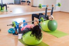 Задний взгляд 2 женщин поднимая штангу лежа на шарике стабильности пока работающ в спортзале стоковая фотография rf