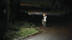 Задний взгляд корзины нося африканского человека с одеждами, 2 мальчиками идя около мужчины через дорогу на ноче в дожде акции видеоматериалы