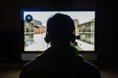 Задний взгляд красивого молодого gamer играя видеоигры FPS дома в темной комнате стоковое изображение