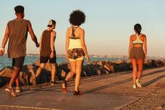 Задний взгляд 4 людей спорт идя outdoors Стоковое фото RF