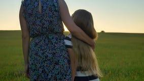 Задний взгляд матери обнимая маленькую дочь с длинными белокурыми волосами, стоящ в середине пшеничного поля и наблюдать акции видеоматериалы