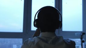 Задний взгляд молодого бизнесмена в наушниках использует планшет окном в вечере 3840x2160, 4K акции видеоматериалы