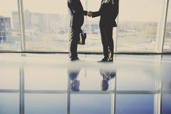 Задний взгляд молодого бизнесмена смотрит из панорамного окна и говорит телефоном Стоковая Фотография