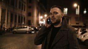Задний взгляд молодого красивого человека идя через улицу в вечере и используя smartphone, разговаривая с другом видеоматериал