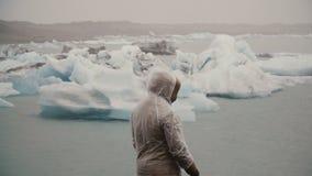 Задний взгляд молодого человека в плаще стоя в лагуне льда в Исландии Турист исследуя известное визирование самостоятельно сток-видео