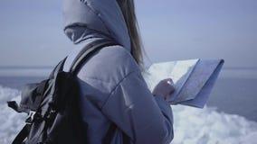 Задний взгляд молодой белокурой женщины в теплой куртке с рюкзаком стоя на леднике проверяя с картой E видеоматериал