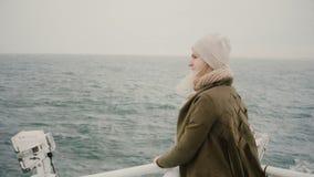 Задний взгляд молодой белокурой женщины стоя на корабле и смотря тоскующе на море, исследуя Исландию сток-видео