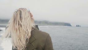 Задний взгляд молодой белокурой женщины стоя на черном пляже в Исландии Свобода: турист поднимая вверх по рукам, волна волос на в акции видеоматериалы