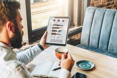 задний взгляд Молодой бородатый бизнесмен в рубашке сидит на таблице, используя планшет с диаграммами, диаграммы, диаграммы Стоковые Изображения RF