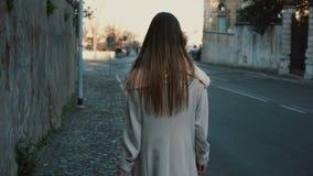 Задний взгляд молодой дамы идя в центр города самостоятельно Женщина при длинные волосы идя около дороги, наслаждаясь днем Стоковые Изображения