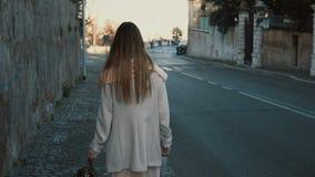 Задний взгляд молодой дамы идя в центр города самостоятельно Женщина при длинные волосы идя около дороги, наслаждаясь днем Стоковое Изображение