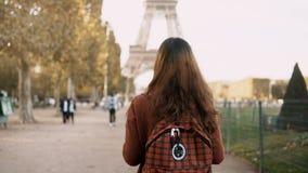 Задний взгляд молодой женщины идя с рюкзаком около Эйфелевой башни в Париже, Франции Турист наслаждаясь взглядом видеоматериал