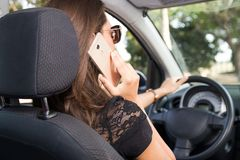Задний взгляд молодой женщины управляя автомобилем и беседами на умном телефоне стоковые фотографии rf