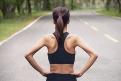 Задний взгляд молодой женщины фитнеса бежать на дороге в утре стоковое изображение rf