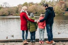 задний взгляд молодой семьи при 2 дет смотря озеро Стоковое Фото