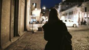 Задний взгляд молодой стильной женщины идя через дезертированную майну поздно на ночу к главной улице, городской дороге видеоматериал