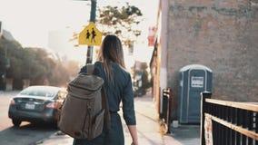 Задний взгляд молодой стильной женщины с рюкзаком идя самостоятельно на заход солнца в лете, тратя время внутри к центру города сток-видео