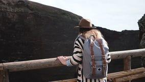Задний взгляд молодой счастливой девушки путешественника с рюкзаком идя до край кратера вулкана Vesuvius в усмехаться Италии видеоматериал