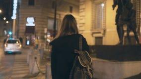 Задний взгляд молодой туристской женщины идя в центр города в вечере, смотря на архитектуре в новом городе видеоматериал