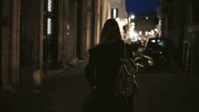 Задний взгляд молодой туристской женщины идя через дезертированную майну без людей к центру города в вечере видеоматериал