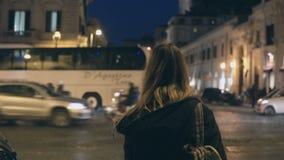 Задний взгляд молодой туристской женщины при рюкзак стоя на дороге движения и смотря вокруг в вечере сток-видео