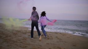Задний взгляд молодых пар бежать с гранатой покрашенного дыма в их руках морем во время захода солнца Потеха, красочная видеоматериал