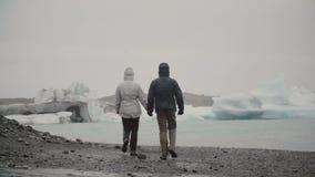 Задний взгляд молодых пар идя в лагуну льда в Исландии Человек и женщина исследуя айсберги и ледники акции видеоматериалы