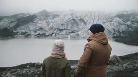 Задний взгляд молодых пар стоя в лагуне льда Путешествующ человек и женщина исследуя Исландию совместно сток-видео