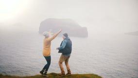 Задний взгляд молодых счастливых пар стоит на береге моря и скакать утехи, обнимая в Исландии сток-видео