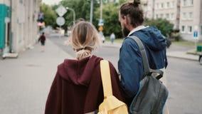Задний взгляд молодых туристских пар идя в центр города, говоря Человек есть фаст-фуд Женщина битника с рюкзаком акции видеоматериалы