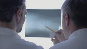 Задний взгляд 2 мужских докторов проверяя рентгеновский снимок, обсуждая Человек в белой робе говоря о человеческих косточках в л видеоматериал
