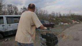 Задний взгляд мужской нажимая магазинной тележкаи на месте захоронения отходов сток-видео