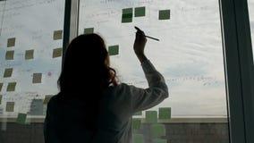 Задний взгляд окна женского работника готовя с липким в современном офисе акции видеоматериалы