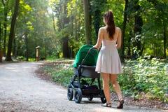 Задний взгляд привлекательных женщин идя с прогулочной коляской в естественной forrest дорожке, молодая мать снаружи с ее newborn стоковые фотографии rf