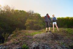 Задний взгляд путешественников или hikers стоит на верхней части горы на sunse стоковое фото rf