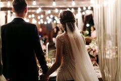 Задний взгляд романтичных пар жениха и невеста на банкете рука об руку Света электрической гирлянды освещают свадьбу стоковые изображения rf