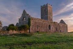 Задний взгляд руин аббатства Клары Augustinian снаружи Ennis монастыря как раз, графство Клара, Ирландия на заходе солнца стоковая фотография