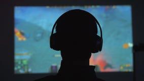 Задний взгляд силуэта молодого человека играет видеоигры в темной комнате смотрит фильм в наушниках 3840x2160 акции видеоматериалы