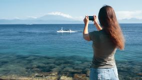 Задний взгляд со стороны путешественника девушки делает видео на телефоне как поплавки шлюпки, замедленном движении сток-видео