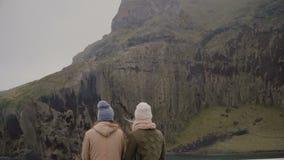 Задний взгляд стильной женщины 2 идя на остров Туристы смотря на зеленой горе, исследуя Исландию видеоматериал