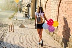 задний взгляд Студент средней школы подростка девушки с воздушными шарами Стоковая Фотография