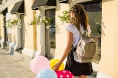 задний взгляд Студент средней школы подростка девушки с воздушными шарами, в школьной форме идет вдоль улицы города Стоковые Фото