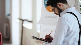 Задний взгляд сфокусировал красивого молодого кавказского бизнесмена писать на бумажном блокноте в занятом современном светлом ра видеоматериал